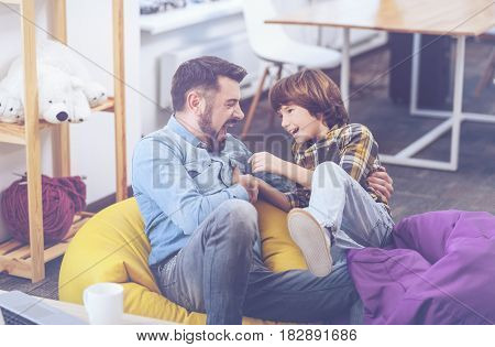 Facetious story. Young father laughing at a child's side-splitter joke and having a tremendous time with his son at home