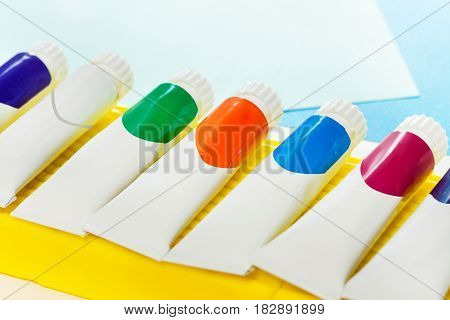 Small tubes of colored gouache with copy-space, laying in a line on the piece of yellow modeling clay