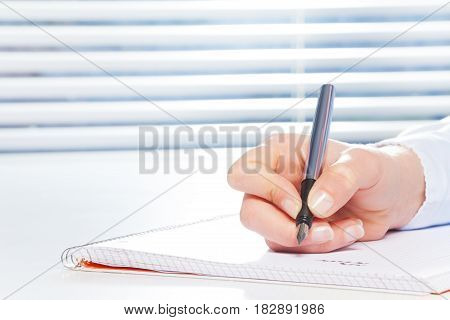 Woman's hand writing on ring-bound notebook with fountain pen at the table