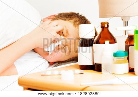 Close-up portrait of sick kid boy with bad cold laying in bed and using paper napkins