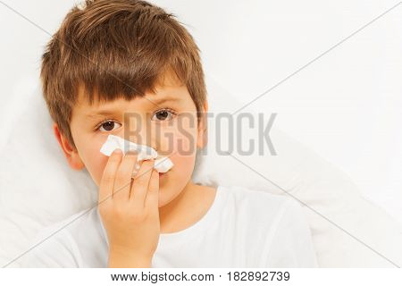 Close-up portrait of sick kid boy with bad cold using paper napkins against blanked background