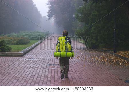 Wanderer with Backpack Walking the City at foggy day