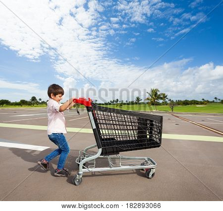 Side view portrait of kid boy pushing empty plastic shopping cart at parking lot