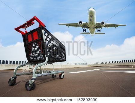 Picture of black empty plastic shopping cart standing at open rooftop parking of a mall with flying air plane in the sky on the background