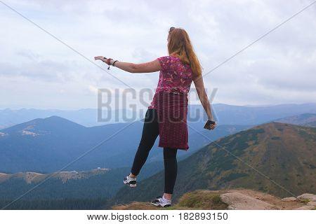 Girl standing on edge of mountain, enjoying the beautiful sunset at Carpathians