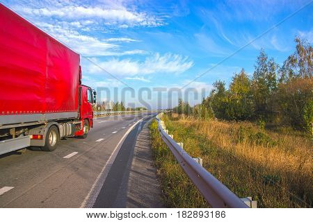 Red truck moving on a highway at bright sky