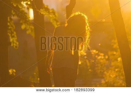 Young girl walks at street on sunrays
