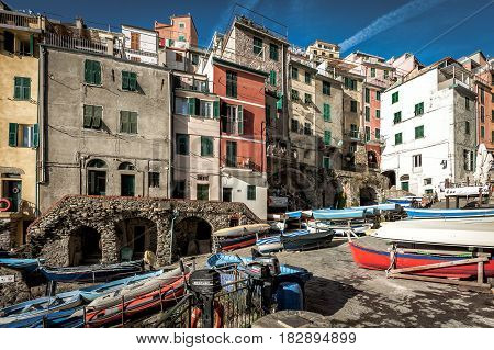RIOMAGGIORE, ITALY - DECEMBER 2016: Wooden boats are moored at coast of Riomaggiore town in Cinque Terre National park, Italy
