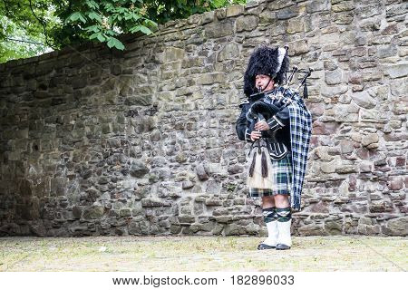 Traditional scottish bagpiper in front of historic wall