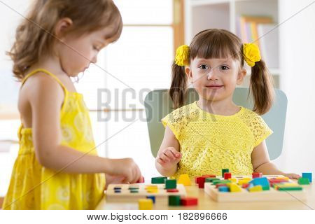 Children kids play with educational toys, arranging and sorting colors and shapes in kindergarten