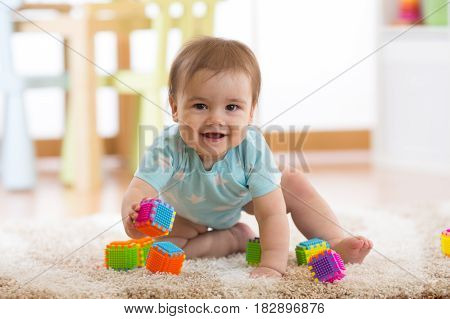 crawling funny baby boy plays on floor at home