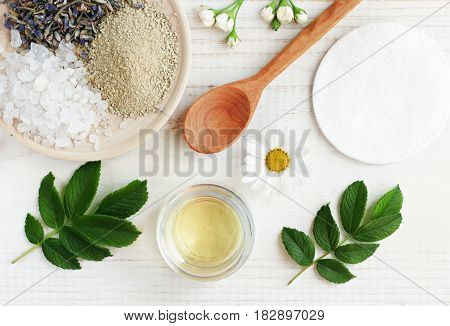 Natural herbal skin care products, top view ingredients. Cosmetic oil, clay, sea salt, herbs, plant leaves. Facial treatment preparation background.