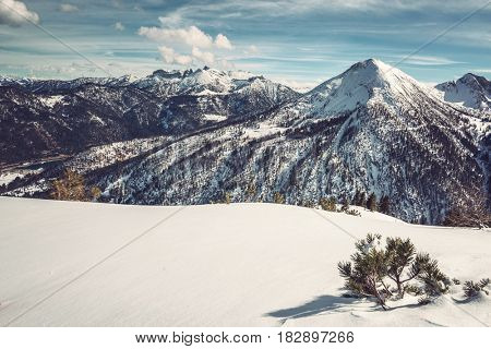Pristine fresh white winter snow in an alpine landscape with snow-capped mountain peaks and valleys