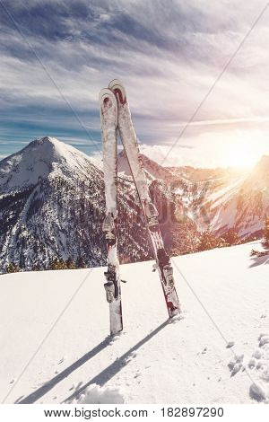 Skis standing upright in fresh white winter snow at sunrise with the glow of the rising sun over steep snow-capped alpine peaks