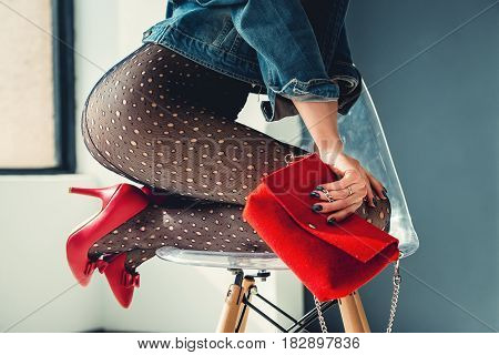 gorgeous girl dressed in a blue jeance jacket, red high heel shoes with red small bag and transparent tights without panties. posing sitting on a stylish armchair. bare shoulders, view from behind