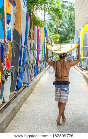 Surfer carrying his board after surfing in Waikiki beach, Hawaii