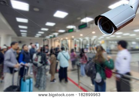 cctv security camera on blurred image of tourist queue at immigration control at airport security technology concept.