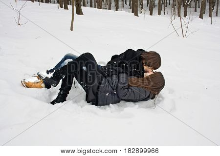 Man and woman in captivity of love kissing lying on the snow