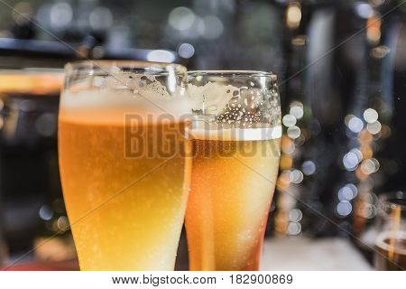 Light beer in a beer glass and dark beer in a small glass lighted with warm light close up