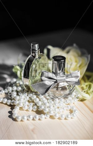 A beautiful bottle of female perfume with a silver bow, a round bottle of light green glass surrounded by pearls stand on a wooden table against a white flower in the dark under the rays of light, vertical frame