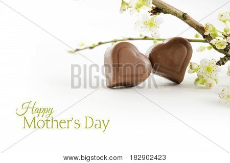Two chocolate hearts and flowering branches isolated with shadow against a white background sample text Happy Mother's Day selected focus narrow depth of field