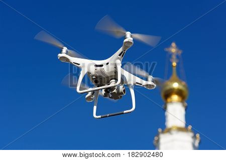 Drone hovering near gilded church dome with orthodox cross at clear blue sky background