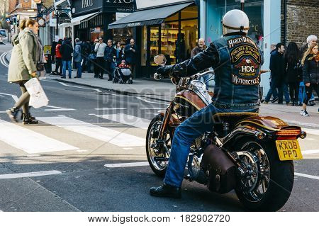 LONDON, UK - MARCH 13, 2016: Man on a Harley Davidson motorcycle with matching logo denim jacket wait for pedestrian crossing a road in Hampstead, London.