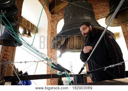 Orel Russia - April 20 2017: Orthodox bell-ringing festival. Bell ringer monk crossing himself after ringing church bells horizontal