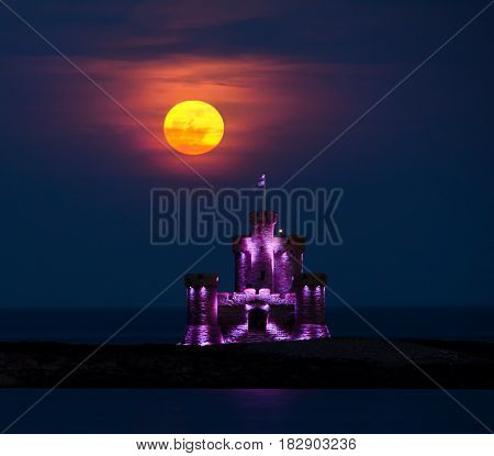 Red Blood moon rising over Tower of Refuge on Isle of Man. Tower is lit up with purple glow.