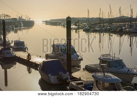 Moored boats on the River Arun at Littlehampton in West Sussex England. Photographed against setting sun