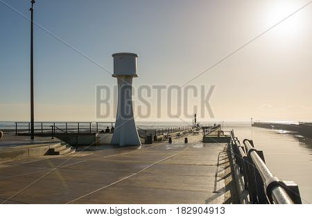 The pier at the entrance to Littlehampton harbour in West Sussex England. Photographed into sun with high key lighting and silhoettes