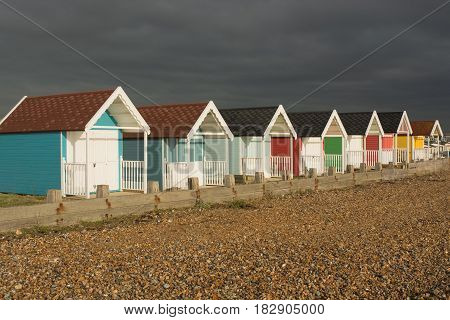 Colourful beach huts on the seafront at Lancing West Sussex England. With very dark and stormy sky