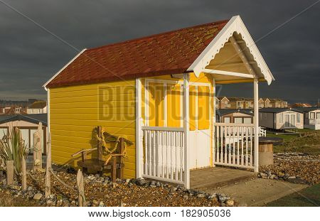 Colourful yellow beach hut on the seafront at Lancing West Sussex England. With very dark and stormy sky
