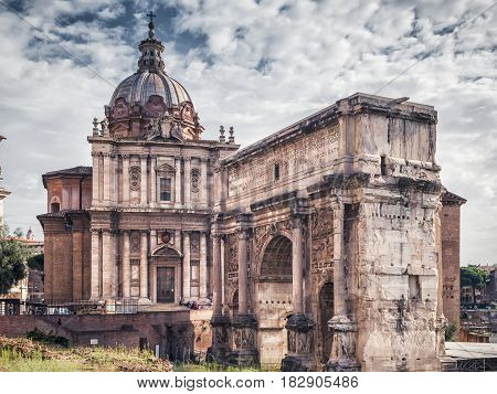 The Roman Forum, Rome, Italy. Triumphal arch of Septimius Severus and medieval church of Santi Luca e Martina. Roman Forum is one of the main tourist attractions of Rome.
