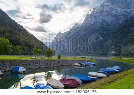 Foggy morning in the Swiss Alps. Mountain lake Klontalersee on background of majestic mountains. Camping on the shore of the lake. Boats on the dock. Glarus canton. Switzerland.