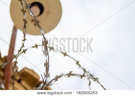 The barbed wire fence and a lantern on the background of the cloudy sky.