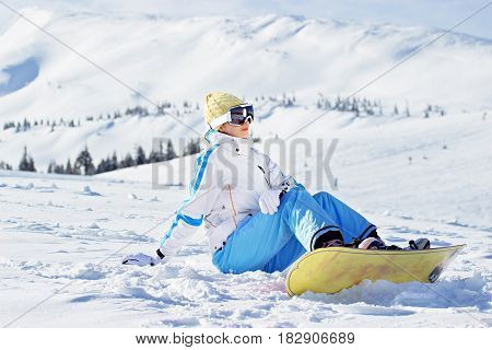 Young Beautiful Girl In White Jacket, Blue Ski Pants And Googles On Her Head Sitting With Snowboard