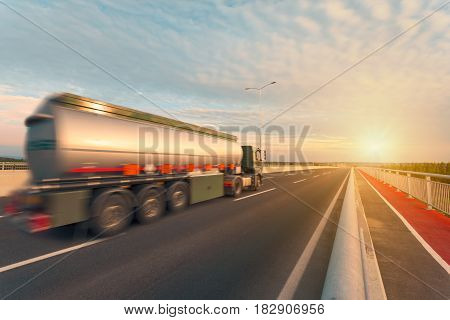 New tanker truck driving fast on open motorway towards the setting sun. Blurred motion photo of transport vehicle on the bridge at beautiful sunset.