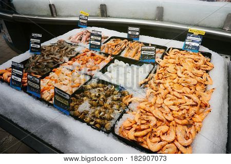 Supermarket stall with langoustine bulot cuit noix saint jacques crevettes calamar rouget barbet - fresh fish counter full with diverse - organic fish meat