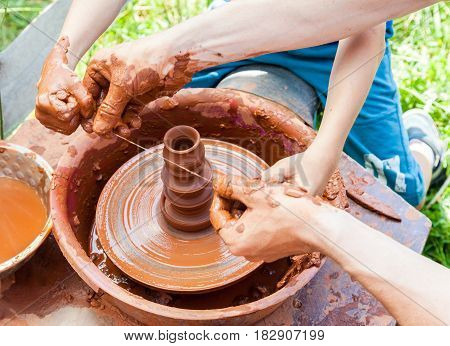 Teacher helps his student to work with red clay. Work on the potter's wheel at the outdoors