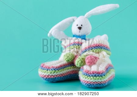 Handmade baby booties and rabbit toy on aquamarine background