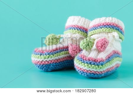 Newborn Announcement. Knitted Baby Booties On Plain Blue Background