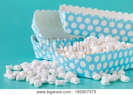 pile of small colored puffy marshmallows isolated on aquamarine background close up