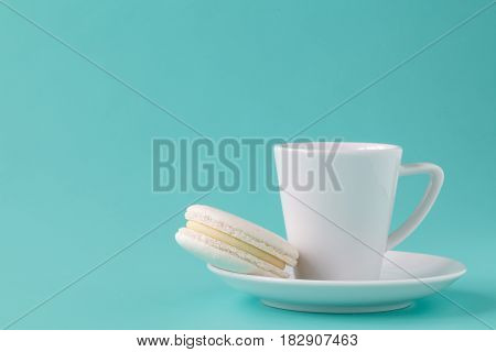 Coffee with one white macaroon on dish