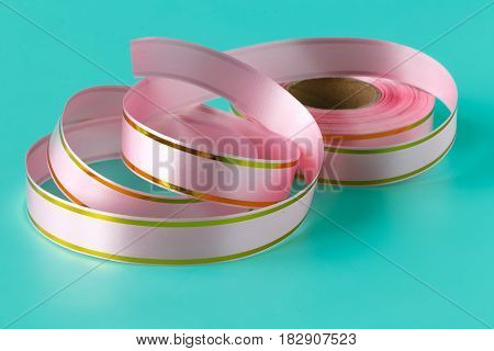 Pink satin colored ribbons on blue background