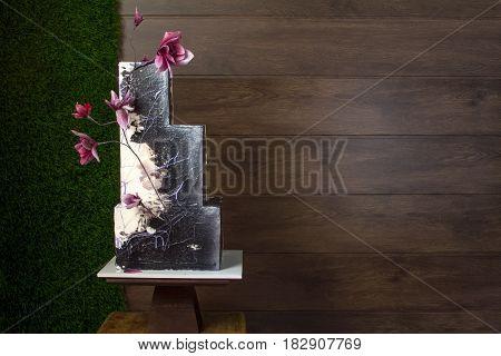 Beautiful tiered birthday cake on a dark wooden background.