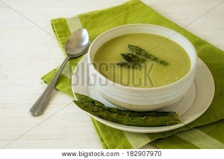 soup from green asparagus in a bowl on a green napkin and a white wooden table copy space selected focus narrow depth of field