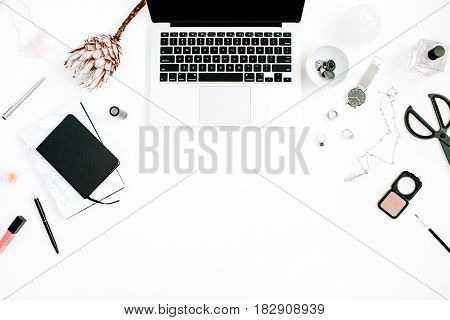 Blogger or freelancer workspace with laptop protea flower notebook and feminine accessories on white background. Flat lay top view minimalistic decorated home office desk. Beauty blog concept.