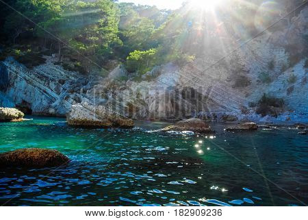 Magic sunshine through the mountains in the blue bay in the Mediterranean Sea