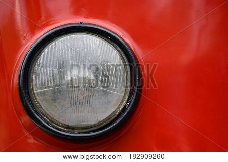 Round headlight of old tram closeup red background